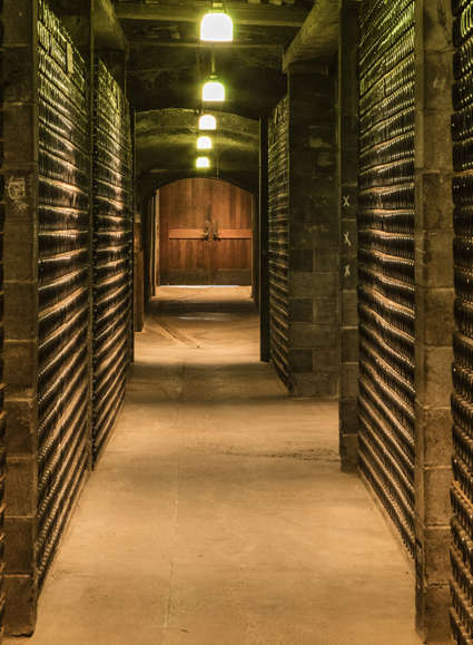 Corridor stacked with fermenting sparkling wine bottles in Schramsberg historic wine caves