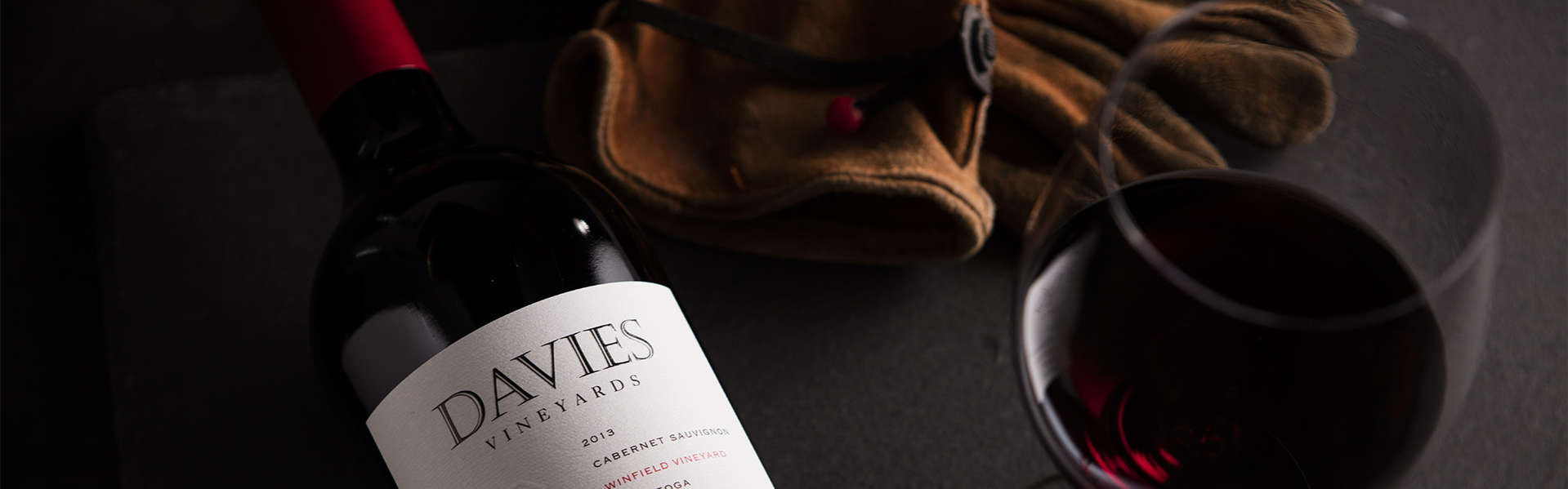 Davies Vineyards 2015 Winfield Vineyard Cabernet Sauvignon on a table with leather work gloves