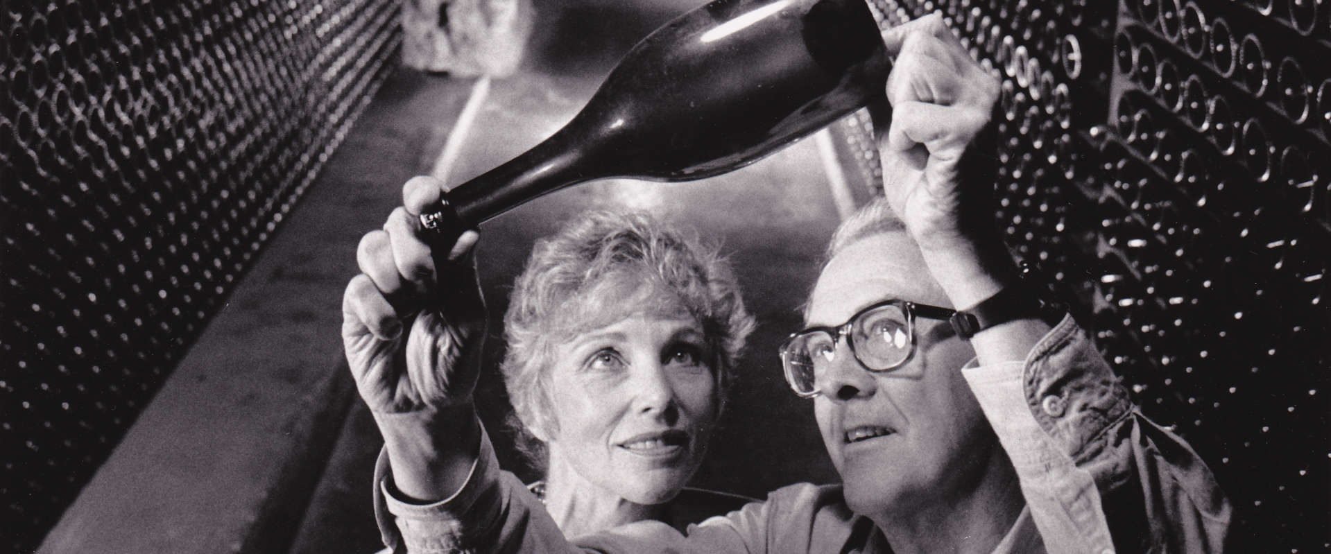 Schramsberg's founder and patriarch, Jack Davies, holds up a sparkling wine bottle to inspect fermentation with Jamie Davies in the historic wine caves, circa 1980