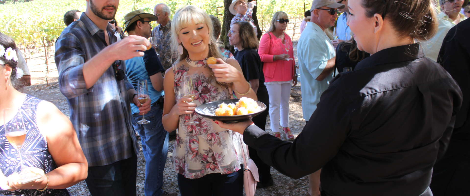 Guests enjoying food and sparkling wine in the redwood grove at a Schramsberg event