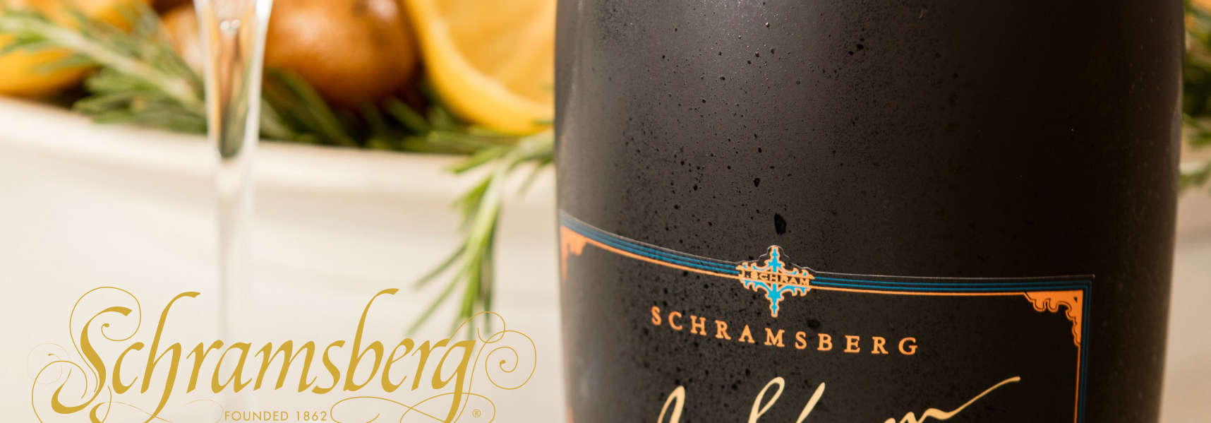 Dinner table with glass and bottle of J. Schram sparkling wine with lemon chicken