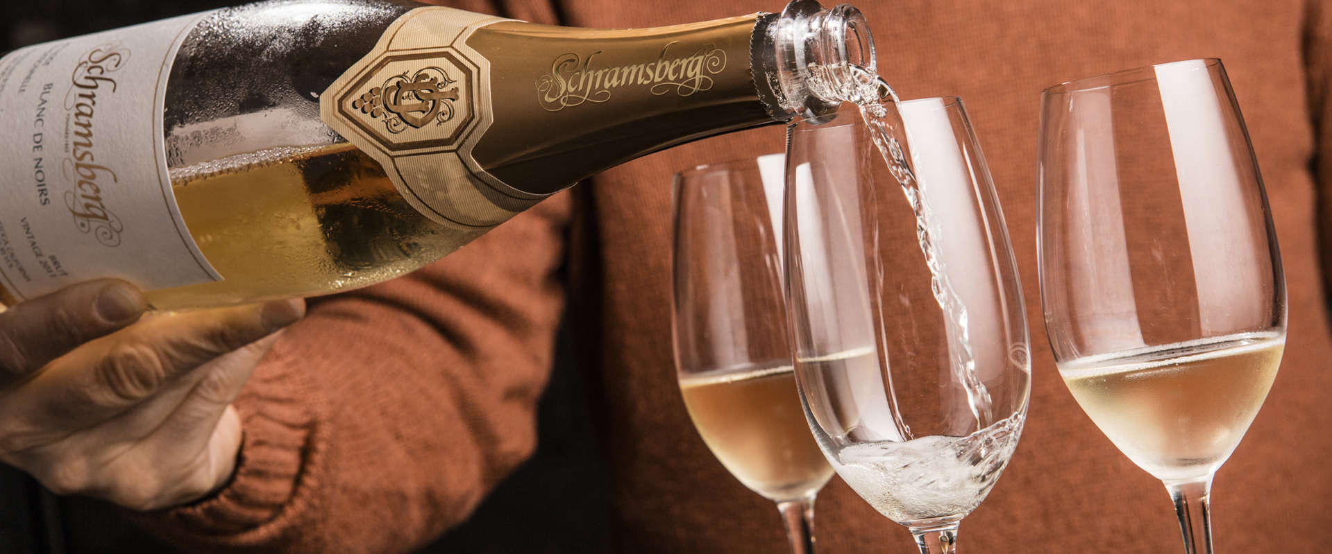 Pouring Blanc de Noirs sparkling wine into three wine glasses