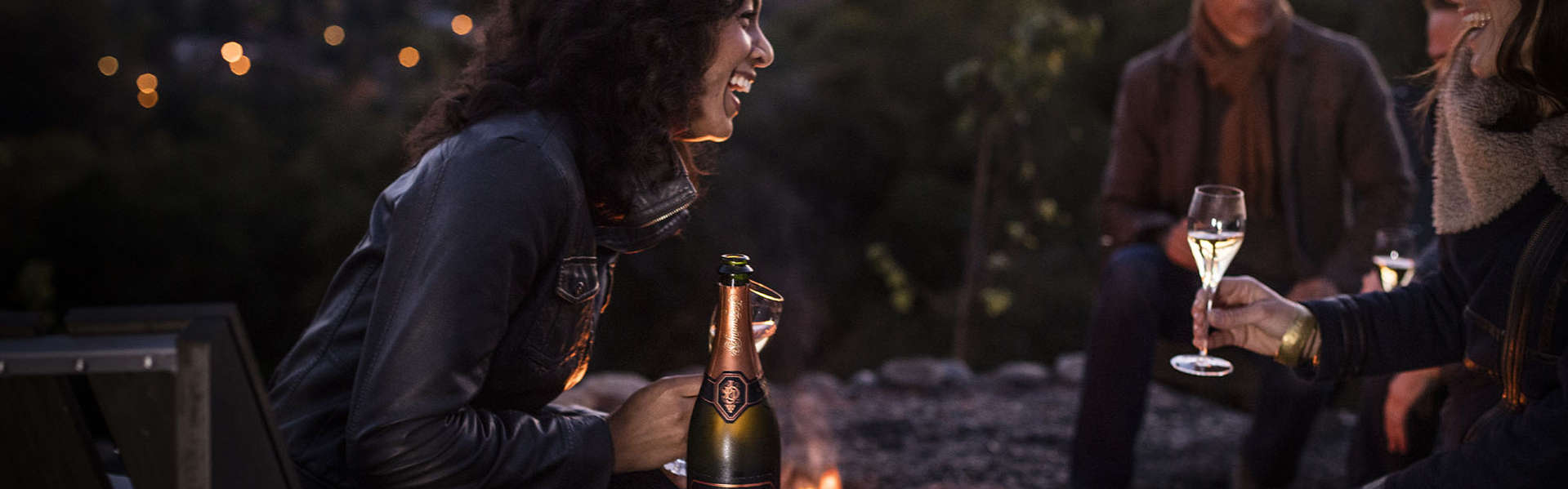 Woman laughing by a fire pit and enjoying Schramsberg sparkling wine