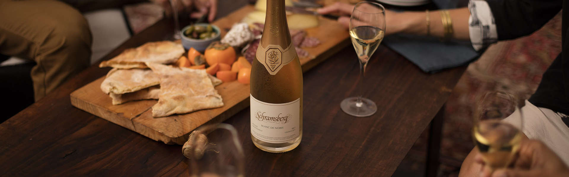 People around a coffee table enjoying Schramsberg Blancs de Noirs sparkling wine paired with a charcuterie board.
