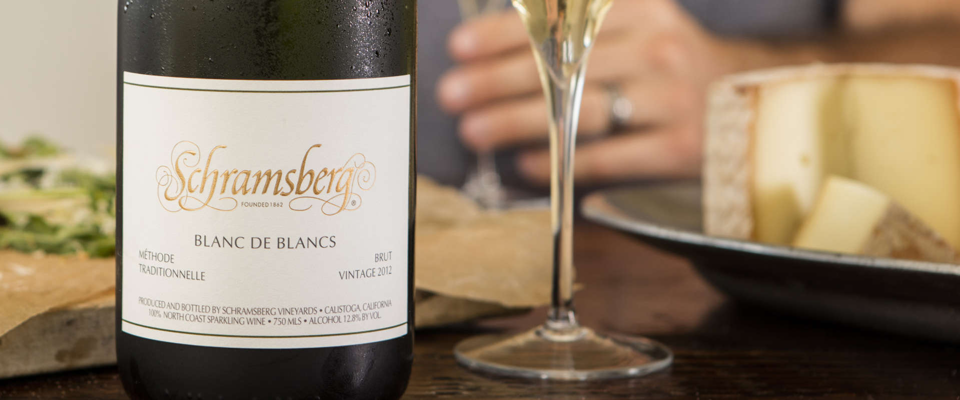 Bottle and glass of Schramsberg Blanc de Blanc sparkling wine paired with cheese