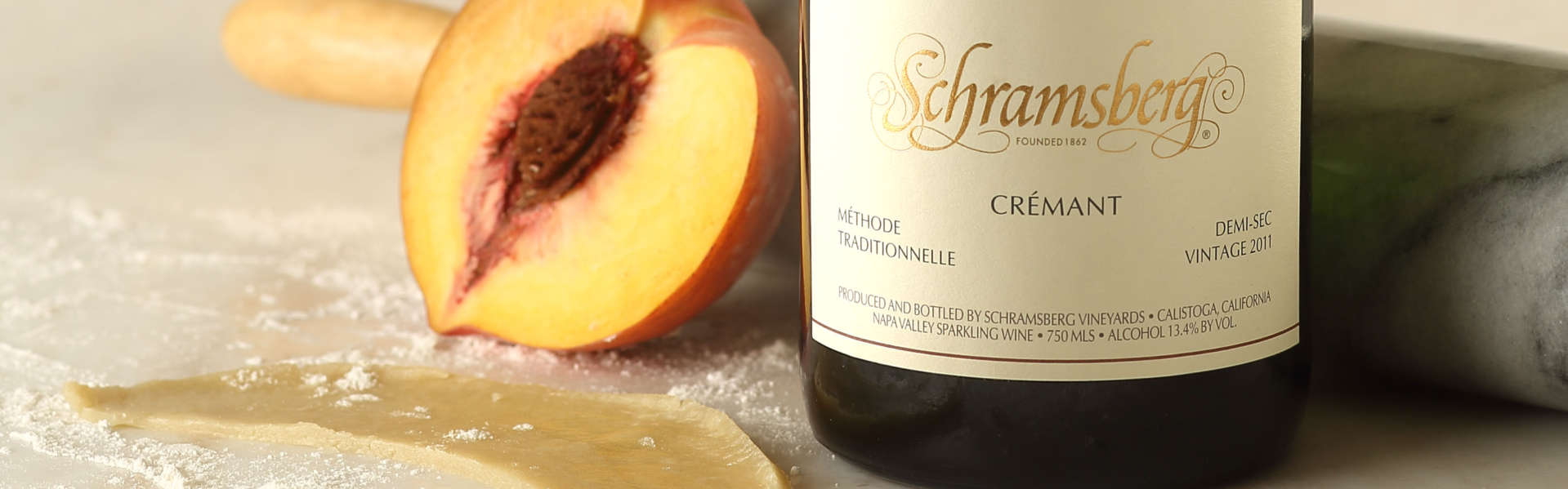 Pastry and sliced peach on table with a bottle of Schramsberg 2011 Cremant Demi-sec sparkling wine